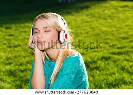 Portrait of young woman sitting on green grass and listening to music with Headphones - stock photo