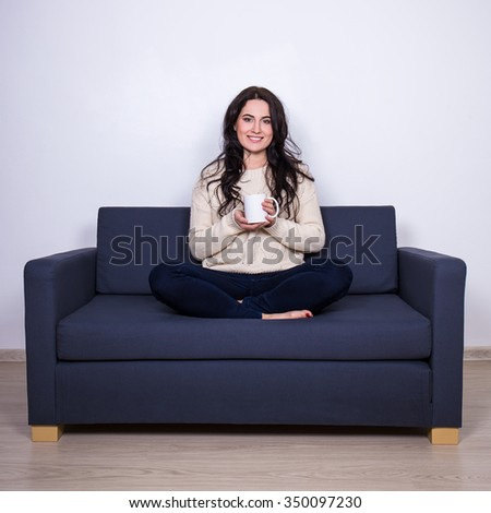 portrait of young woman sitting on sofa with mug of tea or coffee at home