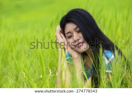 Portrait of young woman sitting on the meadow and looks imagine sweet dream while smiling happy