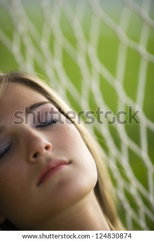 Portrait of young woman sleeping in hammock outdoors - stock photo
