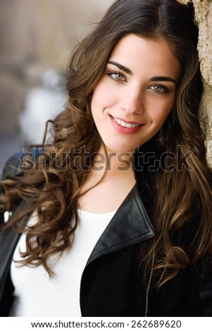 Portrait of young woman smiling in urban background wearing casual clothes - stock photo