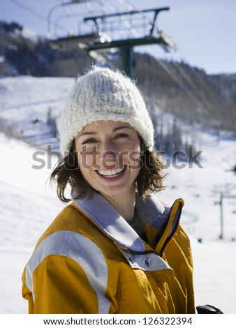 Portrait of young woman smiling on ski resort - stock photo