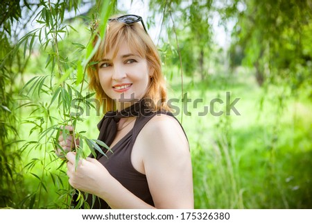 Portrait of young woman smiling outdoors - stock photo