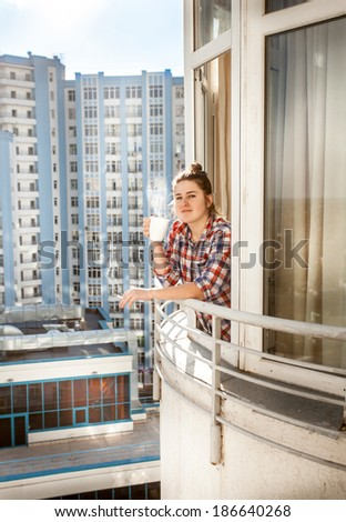 Portrait of young woman smoking and drinking coffee on balcony - stock photo