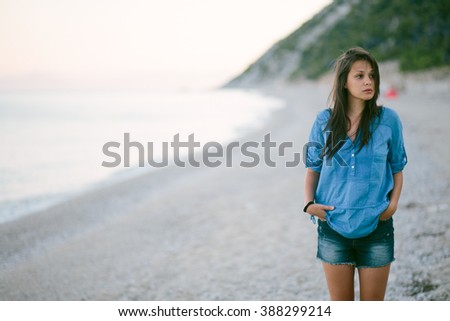 Portrait of young woman standing at the beach - stock photo