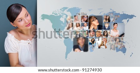 Portrait of young woman standing near big virtual display with world map and lots of photo on it. Network concept - stock photo
