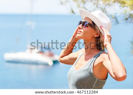 Portrait of young woman standing near the ocean on a summer day.