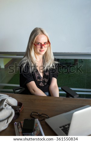 portrait of young woman student in red glasses sitting on the chair