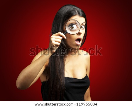 portrait of young woman surprised looking through a magnifying glass over red