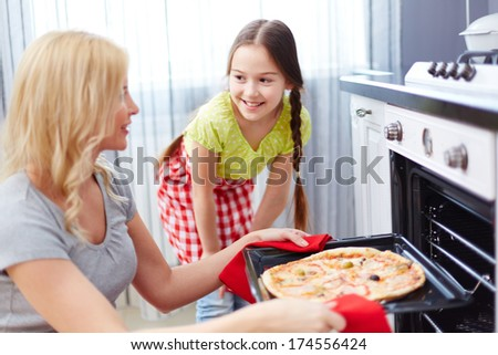 Portrait of young woman taking pizza out of oven with her daughter standing near by - stock photo