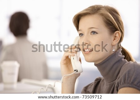 Portrait of young woman talking on landline phone. Looking at camera, smiling. - stock photo