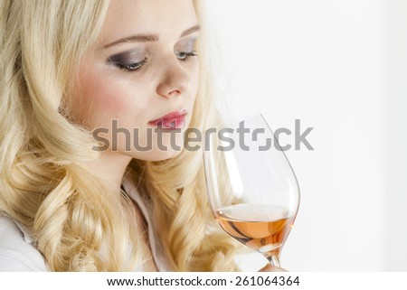 portrait of young woman tasting rose wine