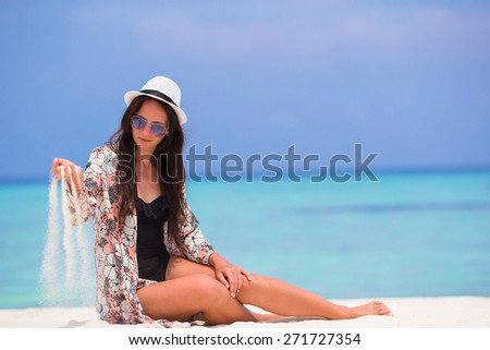 Portrait of young woman throwing sand on beach during summer vacation - stock photo