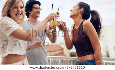 Portrait of young woman toasting cocktail with her friends during a party. Three young friends enjoying in a party. Young man and woman hanging out together. - stock photo