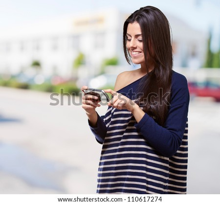 portrait of young woman touching a modern mobile at street - stock photo