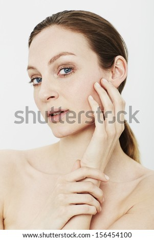 Portrait of young woman touching face in studio