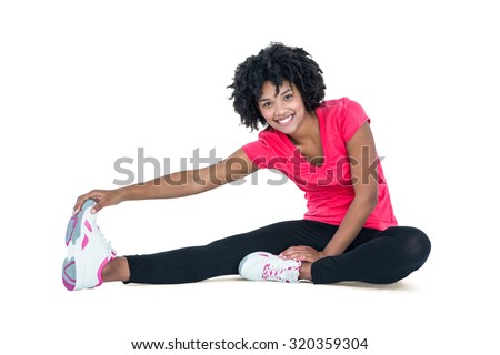 Portrait of young woman touching toes while exercising against white background - stock photo