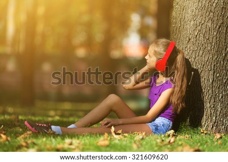 Portrait of young woman under tree and listening to music with headphones.