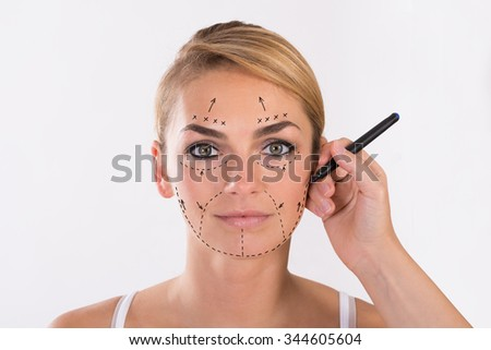 Portrait of young woman undergoing facelift surgery over white background - stock photo