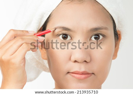 Portrait of young woman using eyebrows pencil