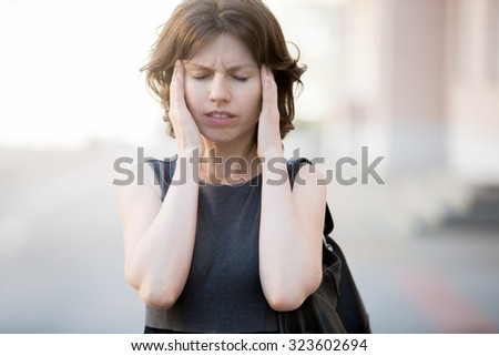 Portrait of young woman walking on the street in summer, frowning, holding her head in hands, having headache, low or high arterial blood pressure, stress - stock photo