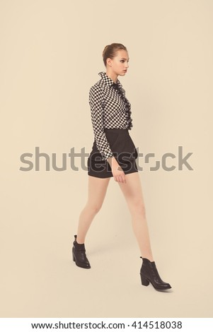 portrait of young woman walking retro background in studio - stock photo