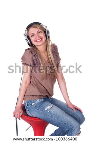 portrait of young woman wearing headphones  and smiling, sitting on red chair . isolated on white background - stock photo