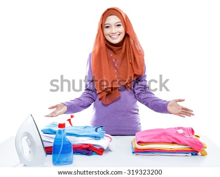 portrait of young woman wearing hijab presenting clean and tidy clothes after ironing isolated on white - stock photo