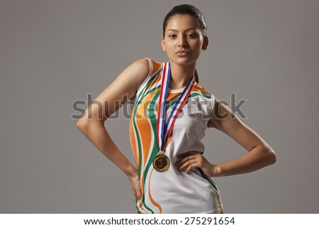 Portrait of young woman wearing medal while posing over gray background - stock photo