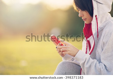 Portrait of young woman wearing sports clothing using mobile telephone.