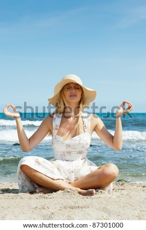 Portrait of young woman wearing summer hat and sophistical elegant dress meditating sitting in lotus pose on sand at beach. Mediterranean sea at the background. Copyspace - stock photo