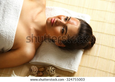 Portrait of young woman while facial cosmetic procedure in spa salon