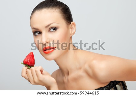 Portrait of young woman with bare shoulders holding ripe strawberry to lips, white studio background. - stock photo