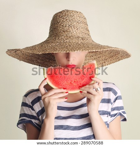 Portrait of young woman with big straw hat and slice of watermelon  - stock photo