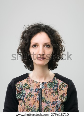 portrait of young woman with blank facial expression, on grey background - stock photo