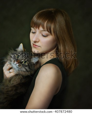portrait of young woman with cat on dark background - stock photo