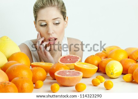 portrait of young woman with citrus fruit - stock photo