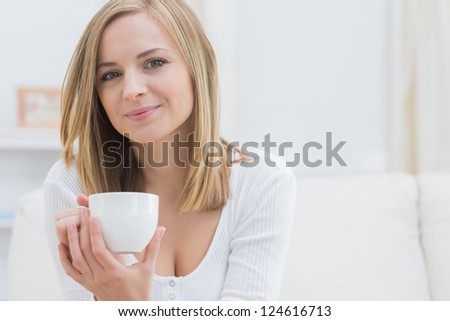 Portrait of young woman with coffee cup at home