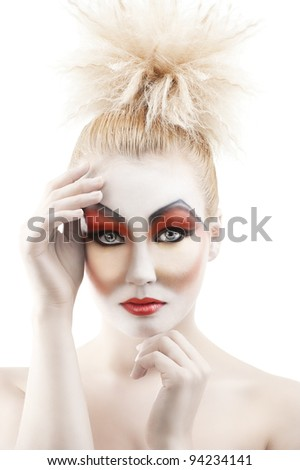 Portrait of young woman with colorful creative make-up like a doll and very cute hair style. she is in front of the camera, looks in to the lens and has both hands near the face