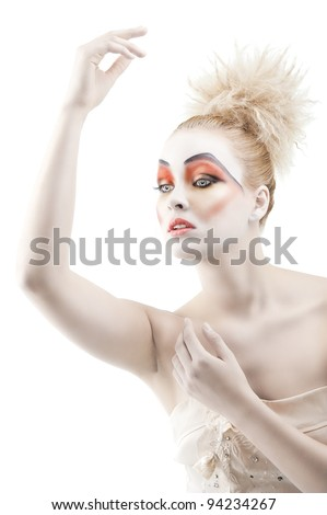 Portrait of young woman with colorful creative make-up like a doll and very cute hair style, she is turned of three quarters and looks at left, her left arm is reised up and she has the right hand