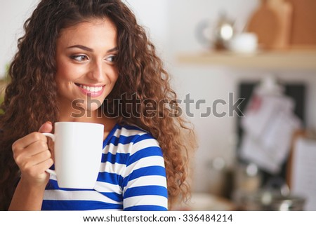 Portrait of young woman with cup against kitchen interior background. - stock photo