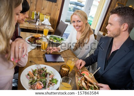 Portrait of young woman with digital tablet having food with colleagues at cafe - stock photo