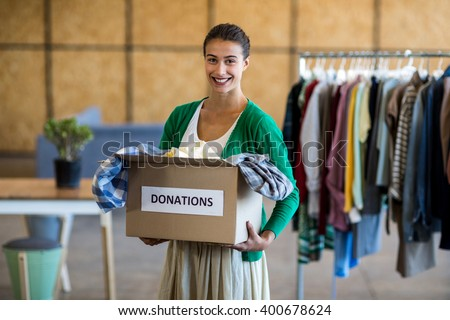 Portrait of young woman with donation box in the office - stock photo