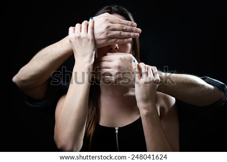 Portrait of young woman with eyes and mouth covered by a male hands. Handling concept. - stock photo