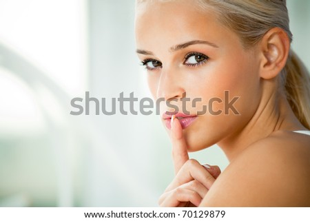 Portrait of young woman with finger on lips, at home - stock photo