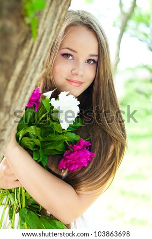 Portrait of young woman with flowers - stock photo