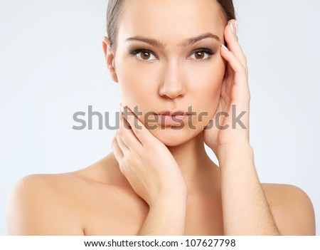 Portrait of young woman with healthy skin touching her face isolated