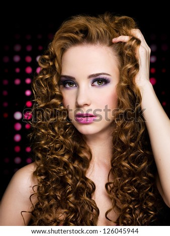 Portrait of young woman with  long curly hair. Blinking Background. - stock photo