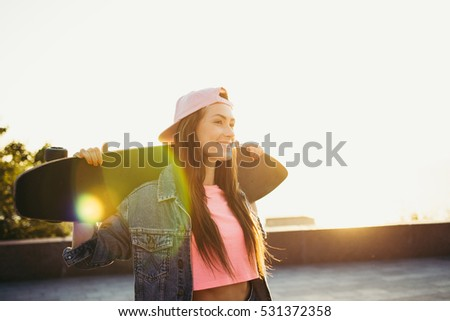 Portrait of young woman with longboard during sunset or sunrise