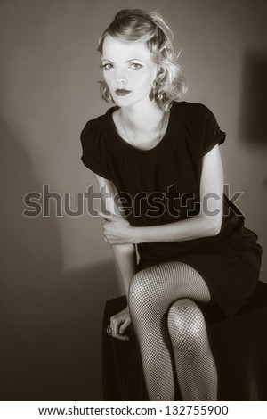 Portrait of young woman with make-up in retro style and  in black dress.